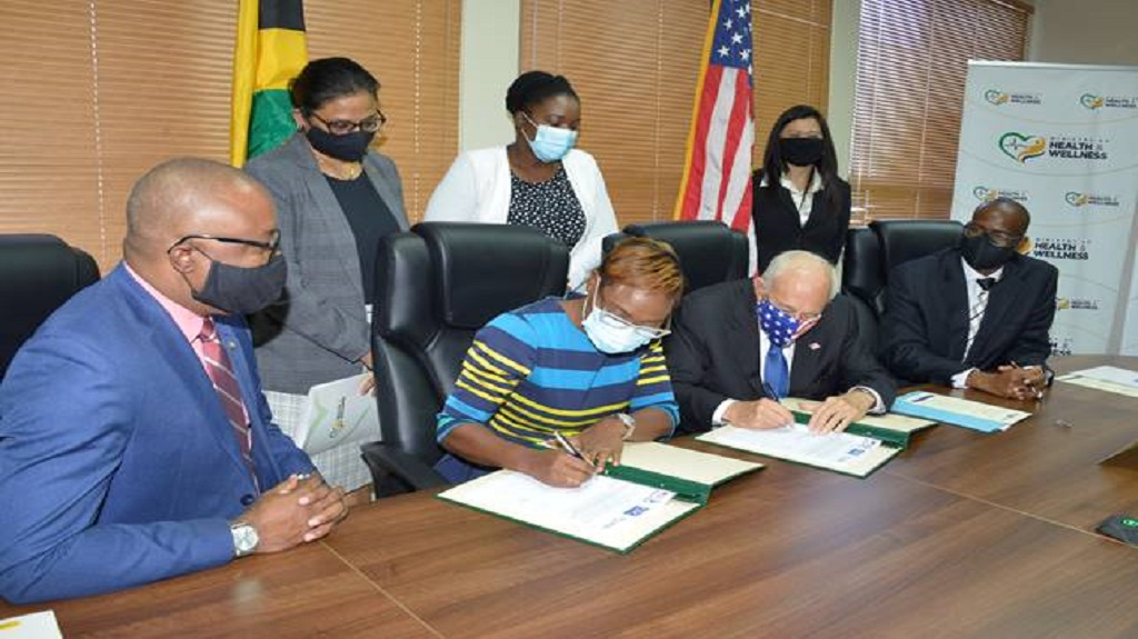 United States Ambassador to Jamaica Donald Tapia (3rd left) alongside State Minister in the Ministry of Health & Wellness (MOH&W), Juliet Cuthbert Flynn (2nd left) sign a multi-million cooperative agreement targeting health.