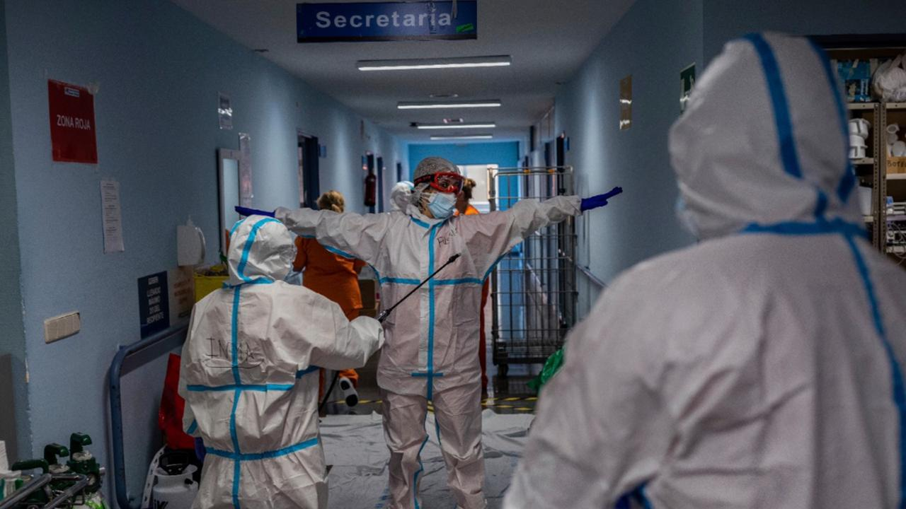 A medical team member is disinfected before leaving the COVID-19 ward at the Severo Ochoa hospital in Leganes, outskirts of Madrid, Spain, Friday, October 9, 2020. At the peak of the first wave, ICU wards were given over to haste, desperation and even cluelessness about what to do. Now, a well-oiled machinery saves some lives and loses others to coronavirus, but without the doomsday atmosphere of March and April. (AP Photo/Bernat Armangue)