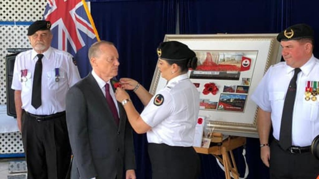 Governor, Martyn Roper receiving the first poppy of Poppy Appeal season