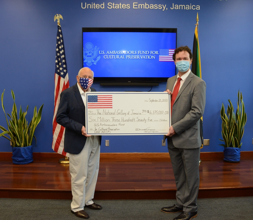 US Ambassador to Jamaica, Donald R. Tapia ( l), presents a symbolic check to Acting Executive Director of the National Gallery of Jamaica (NGJ) Dr Jonathan Greenland.  The NGJ is one of several global recipients of the 2020 US Ambassadors Fund for Cultural Preservation Award.