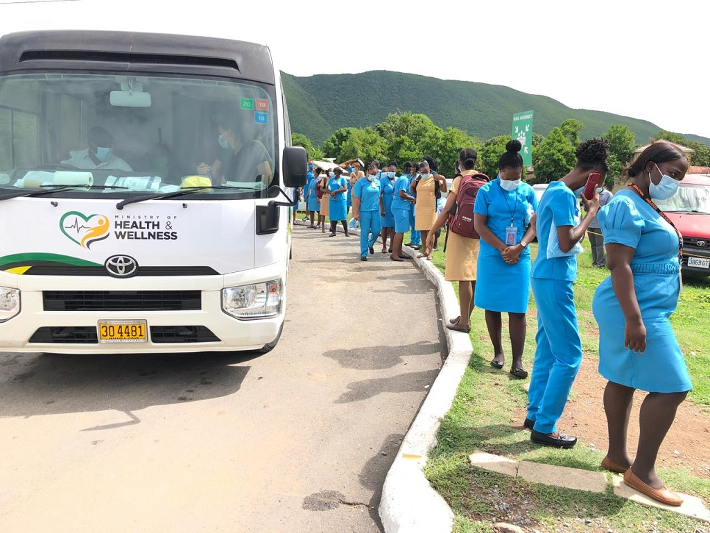 Health care workers outside a mobile testing unit at the Golden Age Home in Vineyard Town, St Andrew on Wednesday.