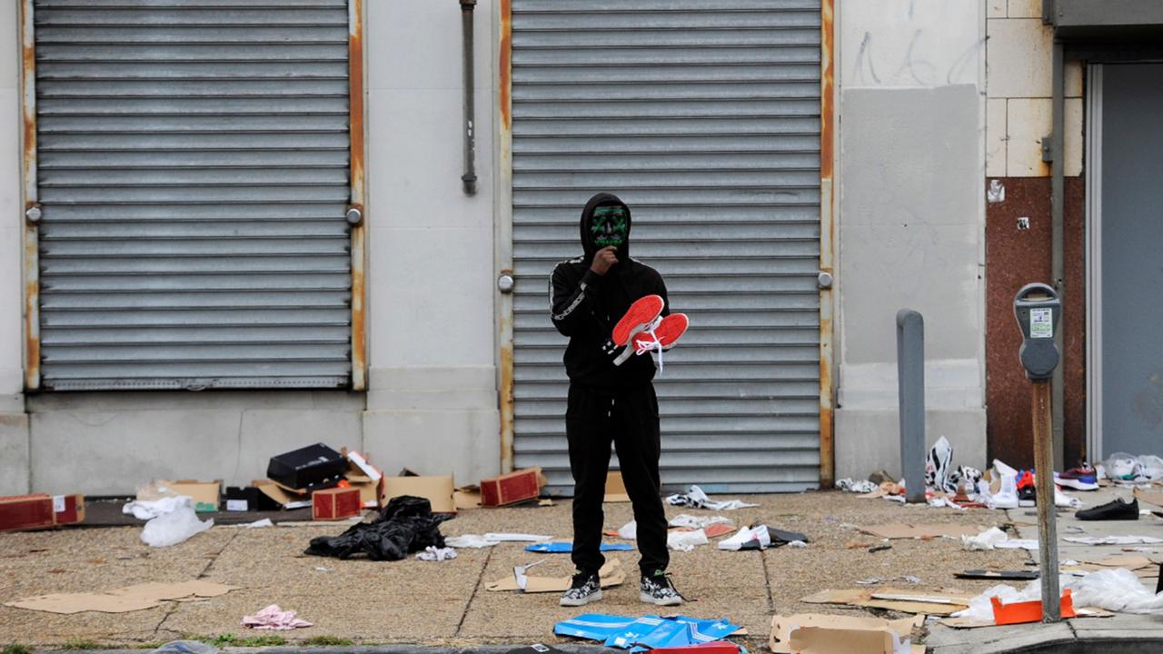 A man stands holds merchandise outside of a damaged store after protest, Tuesday, October 27, 2020, in Philadelphia over the death of Walter Wallace, a Black man who was killed by police in Philadelphia. Police shot and killed the 27-year-old on a Philadelphia street after yelling at him to drop his knife, sparking violent protests that police said injured 30 officers and led to dozens of arrests. (AP Photo/Michael Perez)