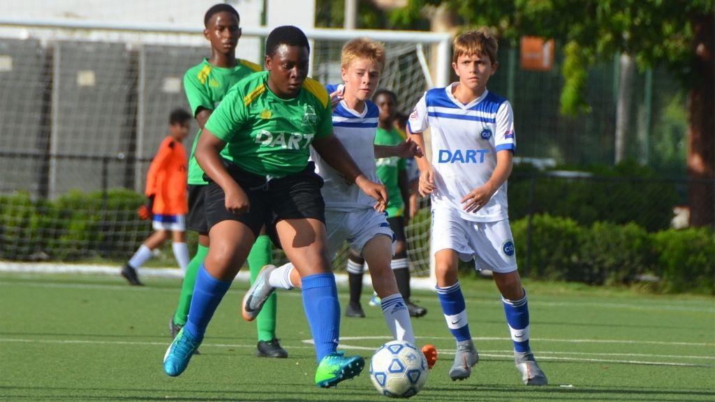 Cayman Academy (green) in action against Cayman International School in the Dart Under 13 Boys high school football league.