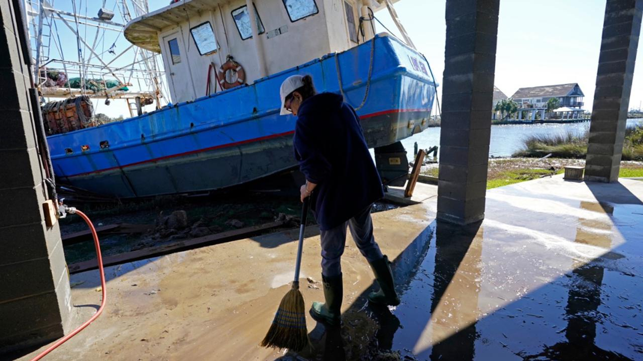 Ray Garcia sweeps water from her home after a boat washed up against it, in Lakeshore, Miss., Thursday, October 29, 2020. Hurricane Zeta passed through Wednesday with a tidal surge that caused the boat to become unmoored. (AP Photo/Gerald Herbert)
