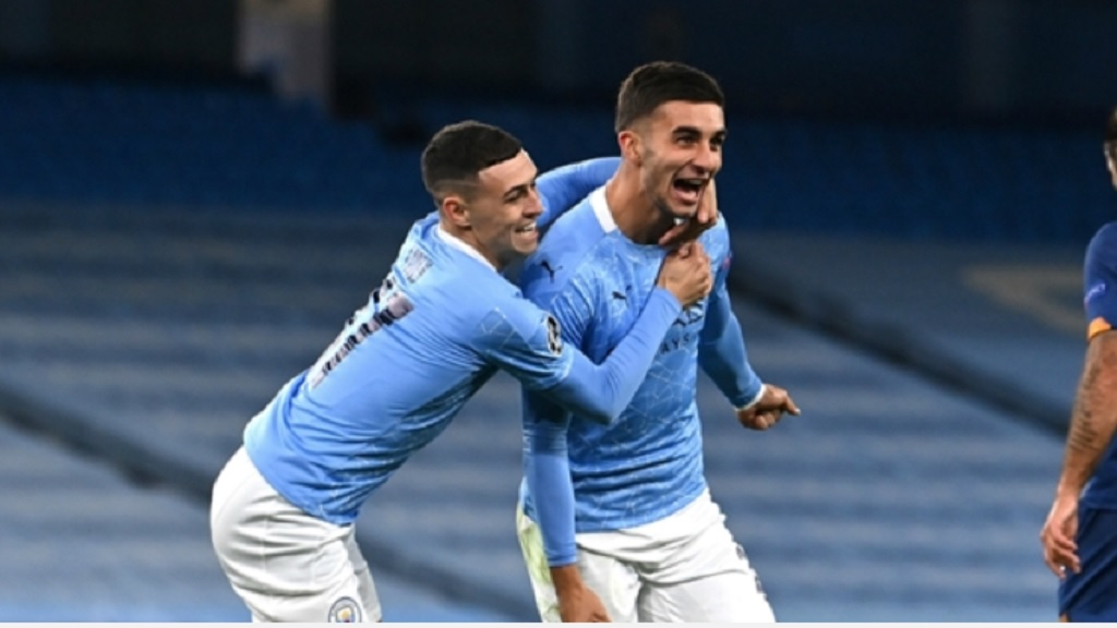 Manchester City's Ferran Torres (right) celebrates after scoring his side's third goal during the Champions League group C  football match against Porto at the Etihad stadium in Manchester, England, Wednesday, Oct. 21, 2020. (Tim Keeton/Pool via AP).