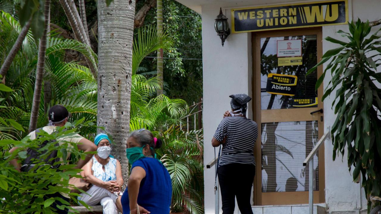 In this June 12, 2020 file photo, people stand outside a Western Union in the Vedado neighbourhood of Havana, Cuba.  (AP Photo/Ismael Francisco, File)