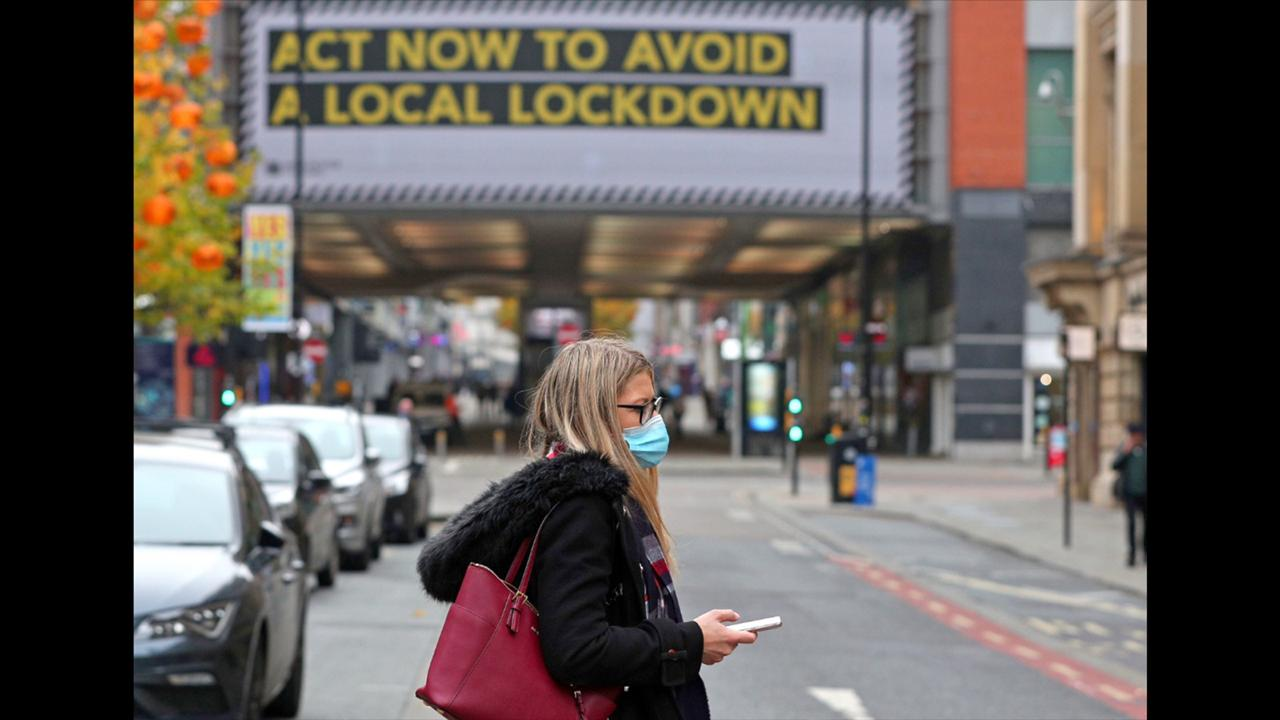 A woman wearing a face mask walks in Manchester, England, Monday, October 19, 2020. (Peter Byrne/PA via AP)