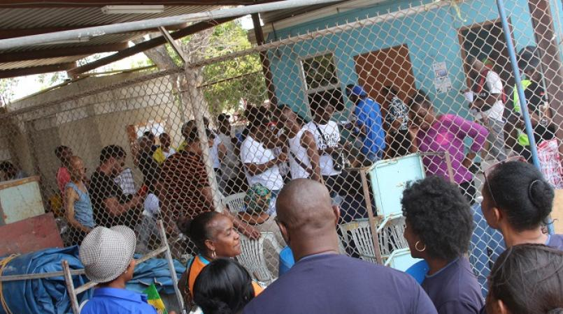 File photo of Jamaicans who were deported being processed behind a fence on the then Mobile Reserve  complex in Kingston.