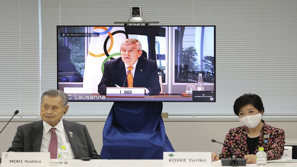In this September 24, 2020, file photo, IOC President Thomas Bach, on the screen, speaks remotely with Tokyo 2020 Organising Committee President Yoshiro Mori, left, and Tokyo Gov. Yuriko Koike, right, during an on-line meeting focused on how to pull off the delayed Tokyo Games, in Tokyo. (Du Xiaoyi/Pool Photo via AP).
