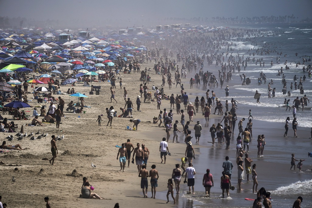 FILE - In this Saturday, September 5, 2020 file photo, people crowd the beach in Huntington Beach, California, as the state swelters under a heat wave. On Wednesday, October 14, 2020, the US National Oceanic and Atmospheric Administration said the Earth reached a record hot September, saying that there's nearly a two-to-one chance that 2020 will end up as the globe's hottest year on record. (AP Photo/Jae C. Hong)
