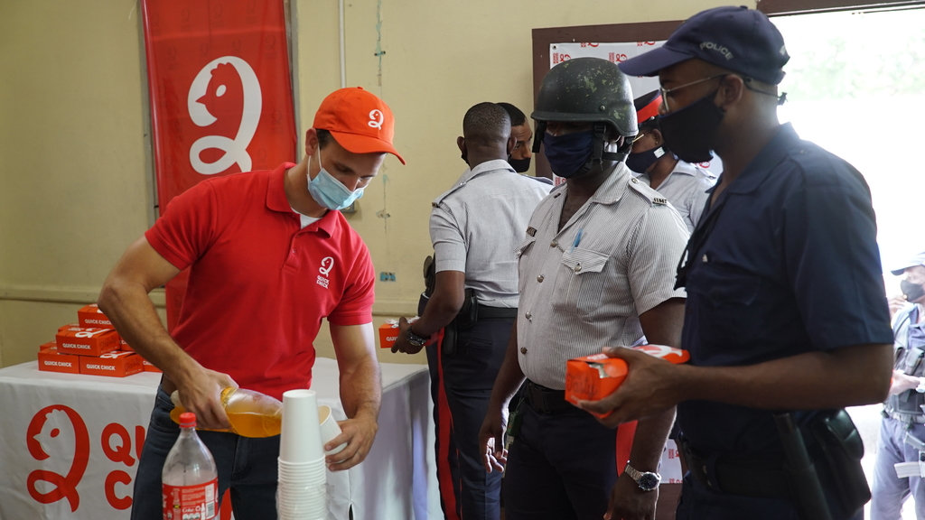 Benjamin Salmon ((left) of Quick Chick serves members of the JCF, Half-Way-Tree Police Station over the National Heroes weekend.