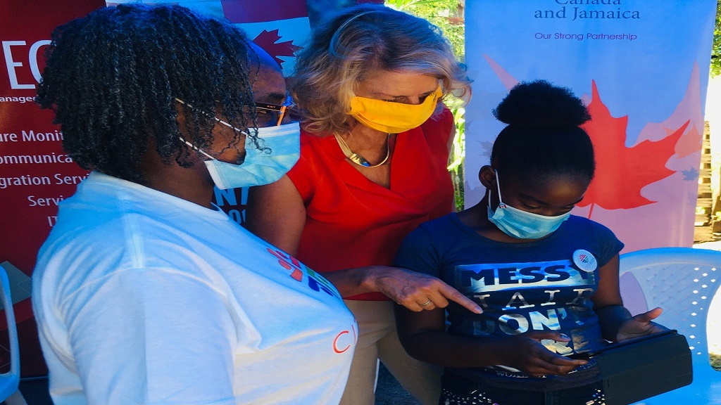igh Commissioner Laurie Peters and Miss Paula Smith, Supervisor for the for the Parade Gardens Homeschool cluster watches on as Daviqua Brown, City Kid and participant in the programme  maneuvers the new learning tablet just received from the Canadian High Commission.