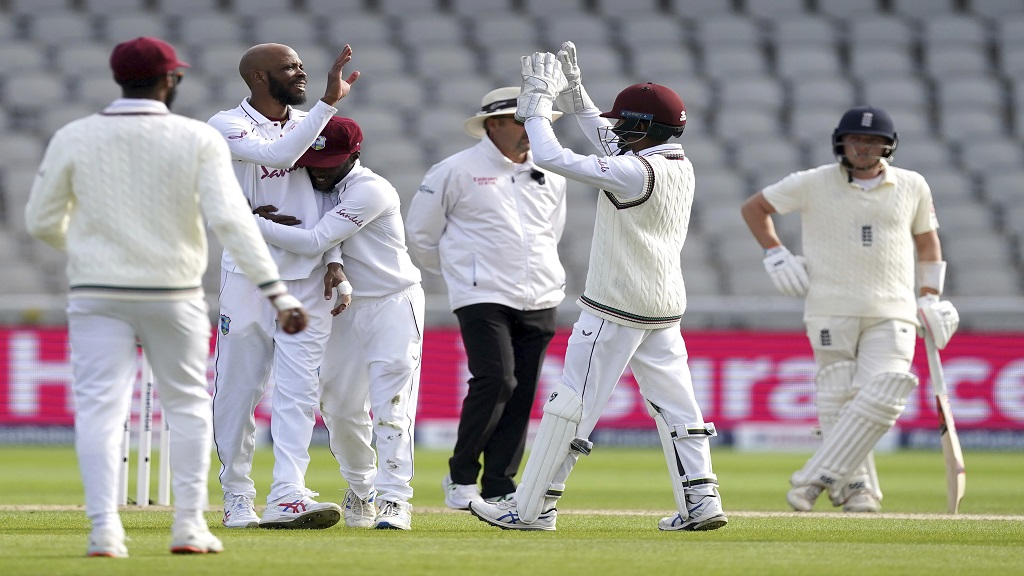 West Indies' Roston Chase, second left, celebrates with teammates the dismissal of England's Sam Curran during the second day of the second cricket Test match at Old Trafford in Manchester, England, Friday, July 17, 2020. (AP Photo/Jon Super, Pool).