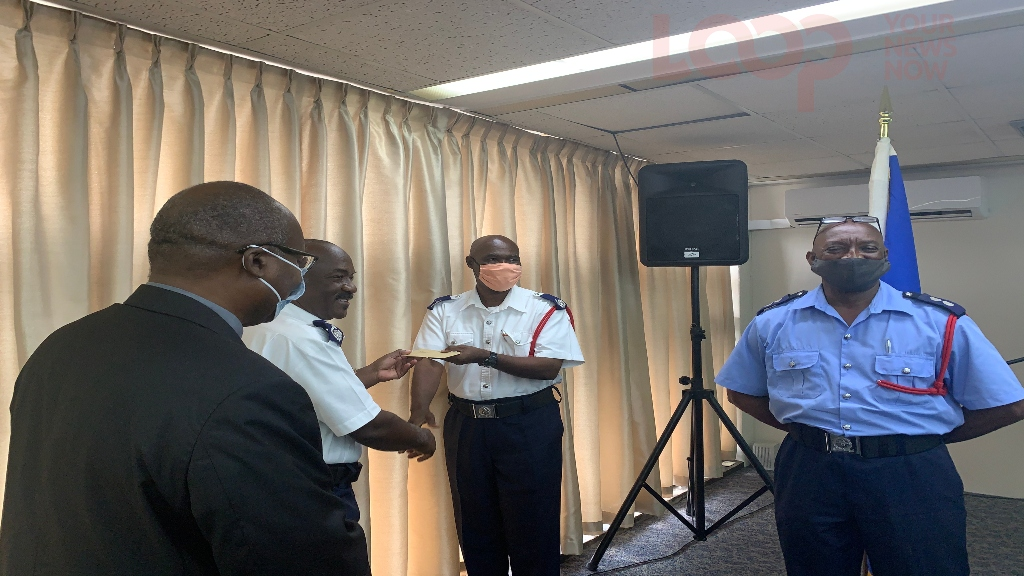 Chief Fire Officer. Errol Maynard, giving Mervin Mayers his appointment letter as Divisional Officer.