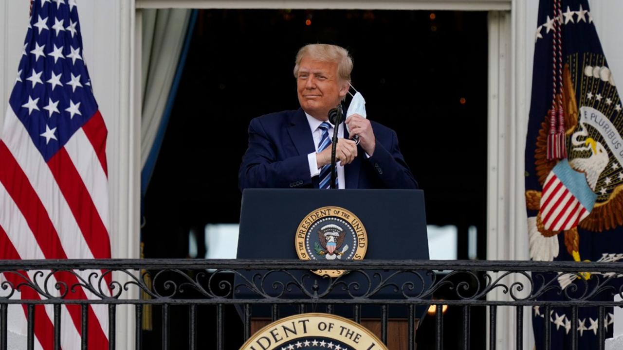 President Donald Trump removes his face mask to speak from the Blue Room Balcony of the White House to a crowd of supporters, Saturday, October 10, 2020, in Washington. (AP Photo/Alex Brandon)