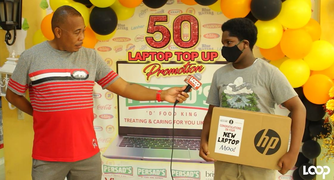 A student collects his prize of a laptop in the Persad's D Food King and Bright Ideas 50 Lucky Students Can Win a Laptop promotion.