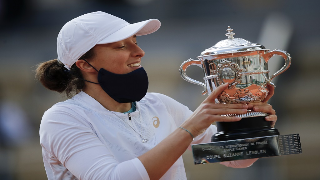 Poland's Iga Swiatek holds the trophy after winning the final match of the French Open tennis tournament against Sofia Kenin of the US in two sets 6-4, 6-1, at the Roland Garros stadium in Paris, France, Saturday, Oct. 10, 2020. (AP Photo/Christophe Ena).