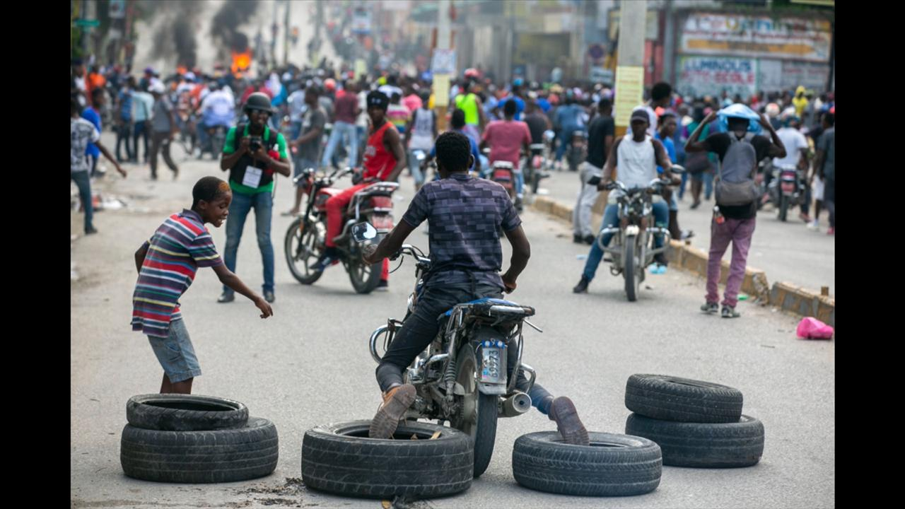 A motorcyclist uses his feet to drag tires into place for a barricade during a protest to demand the resignation of President Jovenel Moise in Port-au-Prince, Haiti, Saturday, October 17, 2020. The country is currently experiencing a political impasse without a parliament and is now run entirely by decree under Moise. ( AP Photo/Dieu Nalio Chery)