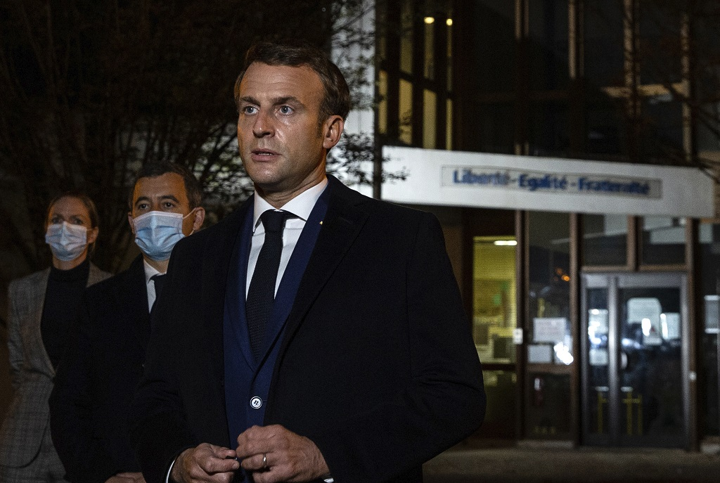 French President Emmanuel Macron, flanked by French Interior Minister Gerald Darmanin, second left, speaks in front of a high school Friday October 16, 2020 in Conflans Sainte-Honorine, northwest of Paris, after a history teacher who opened a discussion with high school students on caricatures of Islam's Prophet Muhammad was beheaded. (Abdulmonam Eassa, Pool via AP)