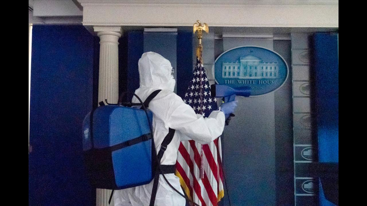 A member of the cleaning staff sprays The James Brady Briefing Room of the White House, Monday, October 5, 2020, in Washington. (AP Photo/Alex Brandon)