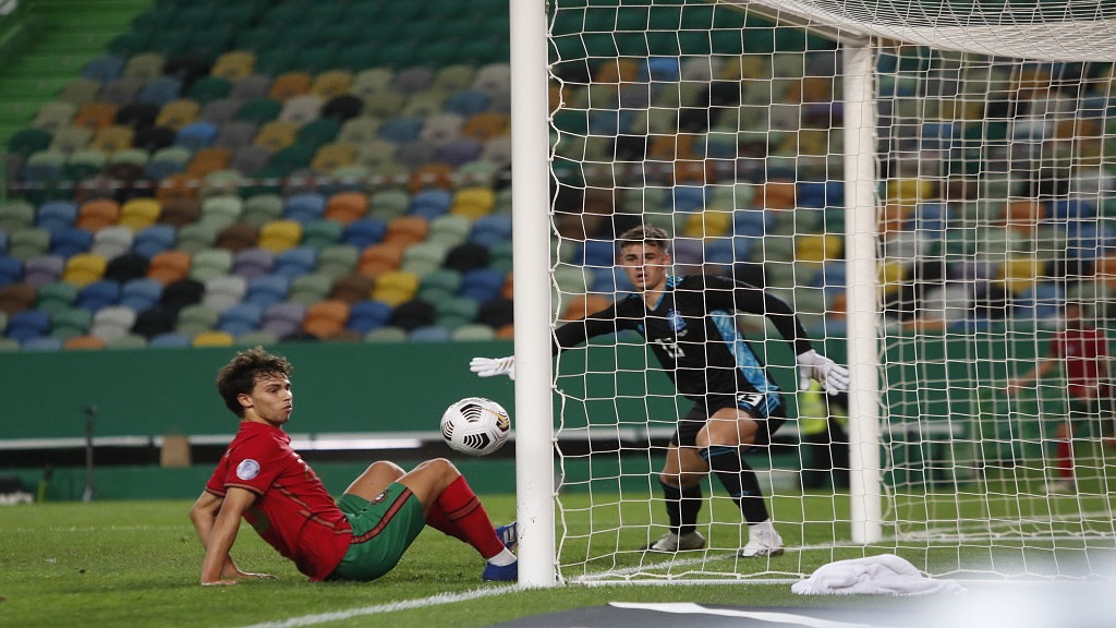 Portugal's Joao Felix, left, and Spain goalkeeper Kepa watch as the ball runs past the goal during their international friendly football match at the Jose Alvalade stadium in Lisbon, Wednesday, Oct. 7, 2020. (AP Photo/Armando Franca).