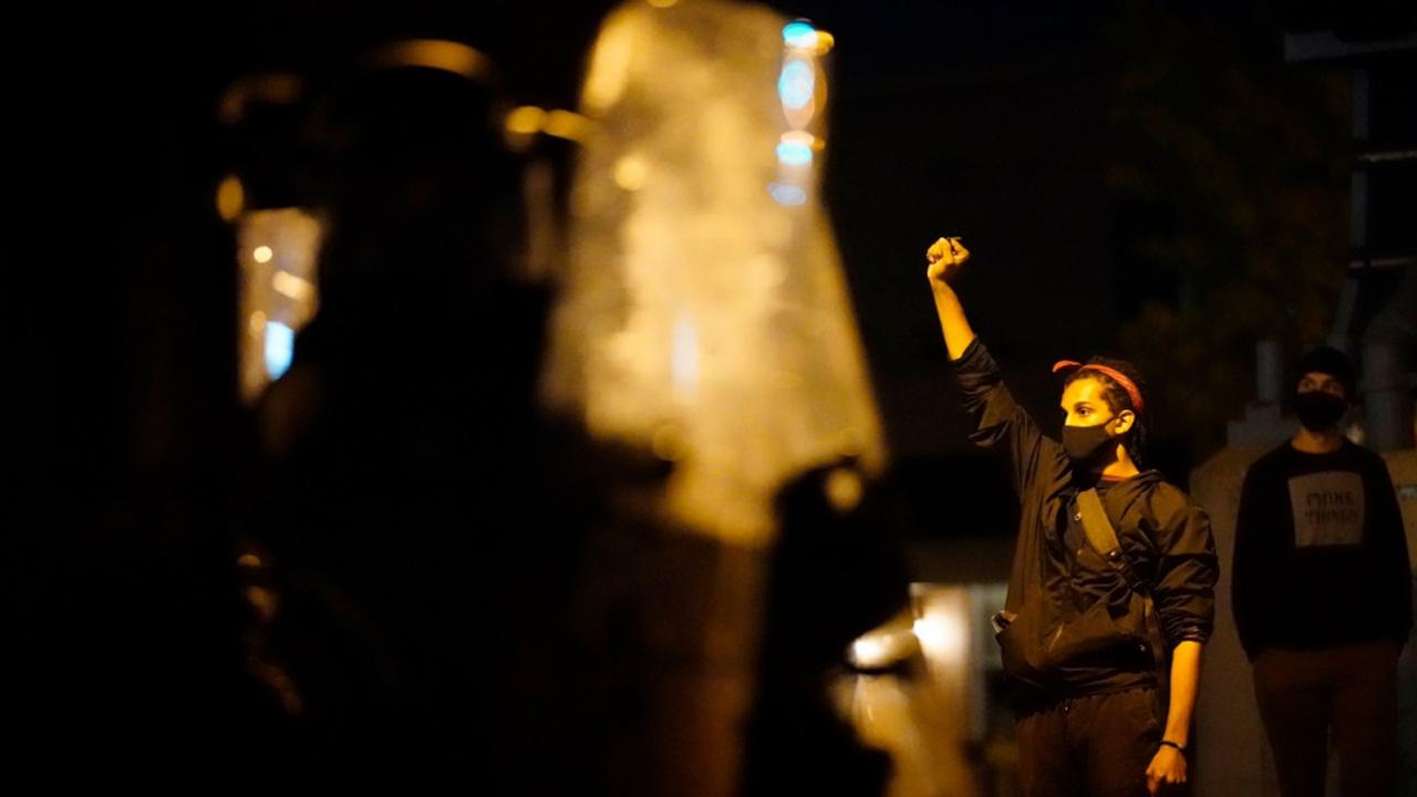 A  demonstrator raises a fist near Philadelphia police in Philadelphia, late Tuesday, October 27, 2020. (AP Photo/Matt Slocum)