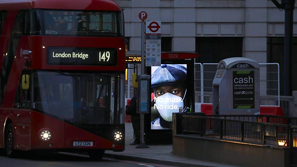"An Uber advert saying ""No mask. No ride."" is displayed at a bus stop on London Bridge before the morning daylight rose in London, Monday, Oct. 12, 2020. In response to the coronavirus' resurgence, British Prime Minister Boris Johnson is expected to announce in Parliament on Monday a three-tier local lockdown system, formally known as ""Local COVID Alert Levels,"" for England, his office said. (AP Photo/Matt Dunham)"