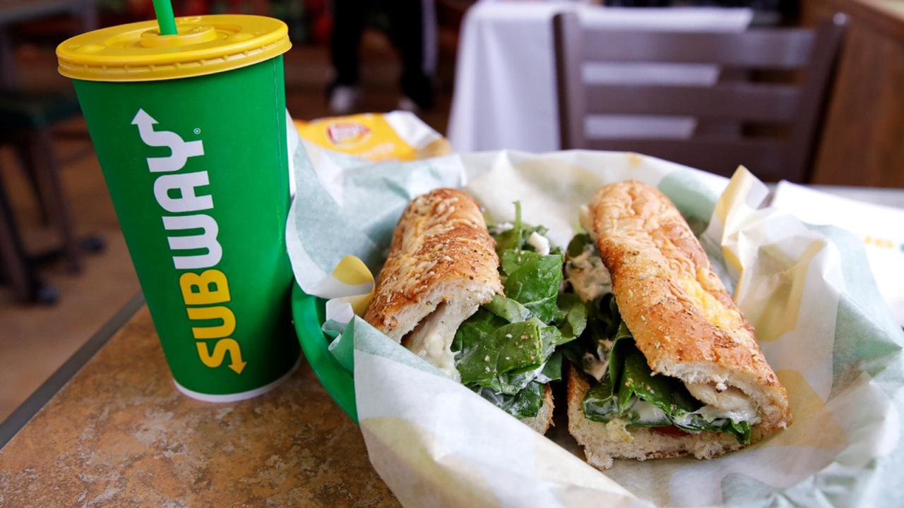 In this Friday, February 23, 2018 file photo, the Subway logo is seen on a soft drink cup next to a sandwich at a restaurant in Londonderry, N.H.. Ireland's Supreme Court has ruled that bread sold by the fast food chain Subway contains so much sugar that it cannot be legally defined as bread. (AP Photo/Charles Krupa, File)