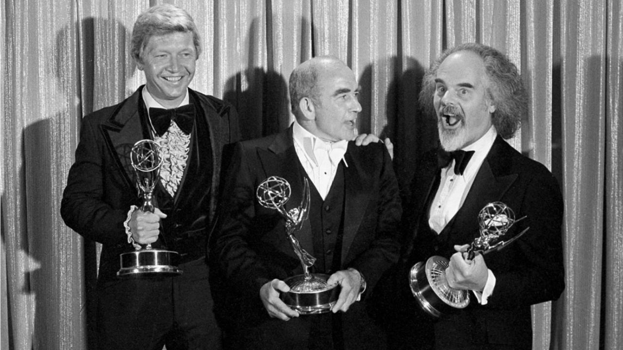 "In this Sunday, September 11, 1977 file photo, Screenwriter William Blinn, left, Ed Asner, centre, and David Greene pose with their Emmy statuettes at the annual Primetime Emmy Awards presentation in Los Angeles. William Blinn, a screenwriter for the landmark TV projects ""Brian's Song"", ""Roots"" and the Prince film ""Purple Rain,"" has died, Thursday, October 22, 2020. He was 83. (AP Photo/File)"