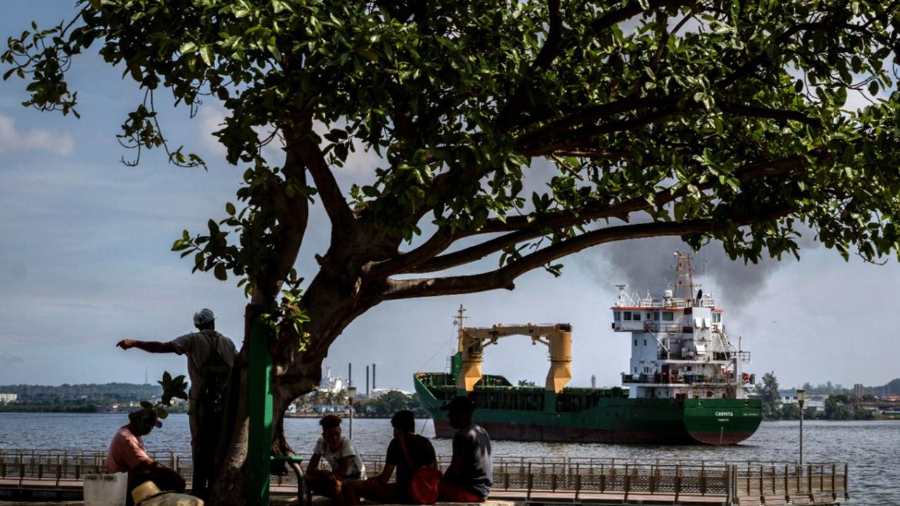 "Fishermen sit in the shade as the ""Carmita"" cargo ship, flying a Panamanian flag, navigates the bay of Havana, Cuba, Thursday, October 22, 2020. Cuba's foreign minister presented the nation's report on the impact of the US embargo over the past year on Thursday. (AP Photo/Ramon Espinosa)"