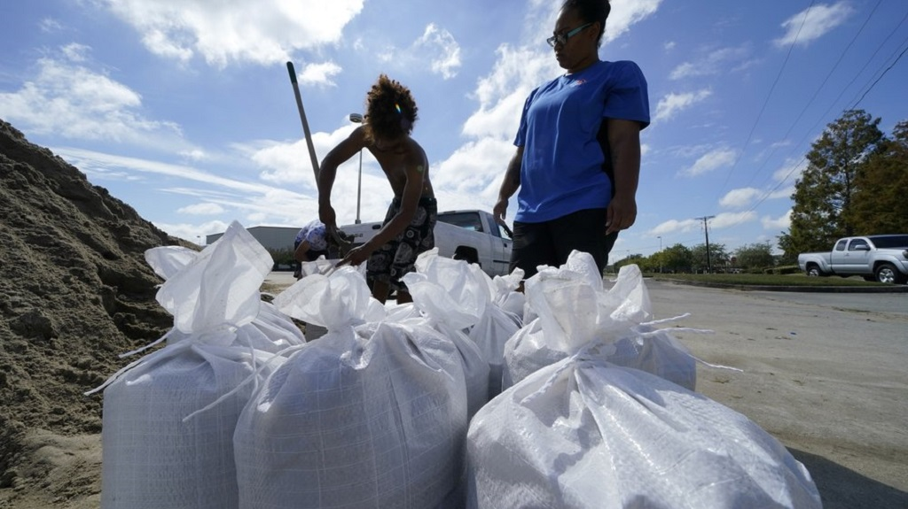 Stephanie Verrett and Jodie Jones fill sandbags to protect their home in anticipation of Hurricane Delta along the Gulf Coast. (Photo: AP/Gerald Herbert)