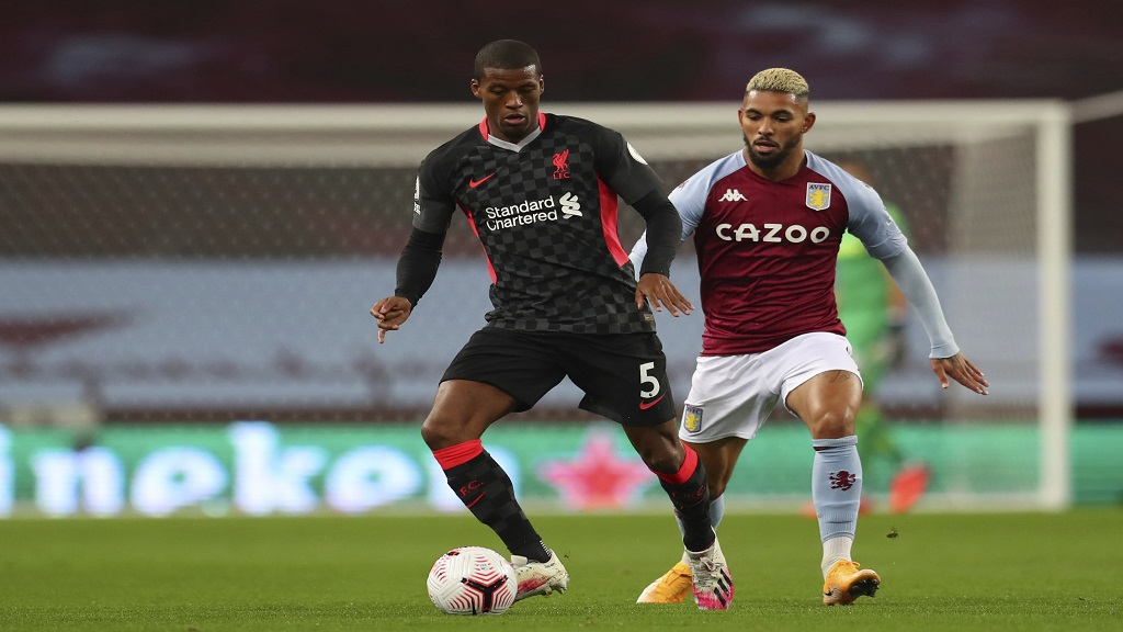 Liverpool's Georginio Wijnaldum, left, is challenged by Aston Villa's Douglas Luiz during the English Premier League football match at the Villa Park stadium in Birmingham, England, Sunday, Oct. 4, 2020. (Cath Ivill/Pool via AP).