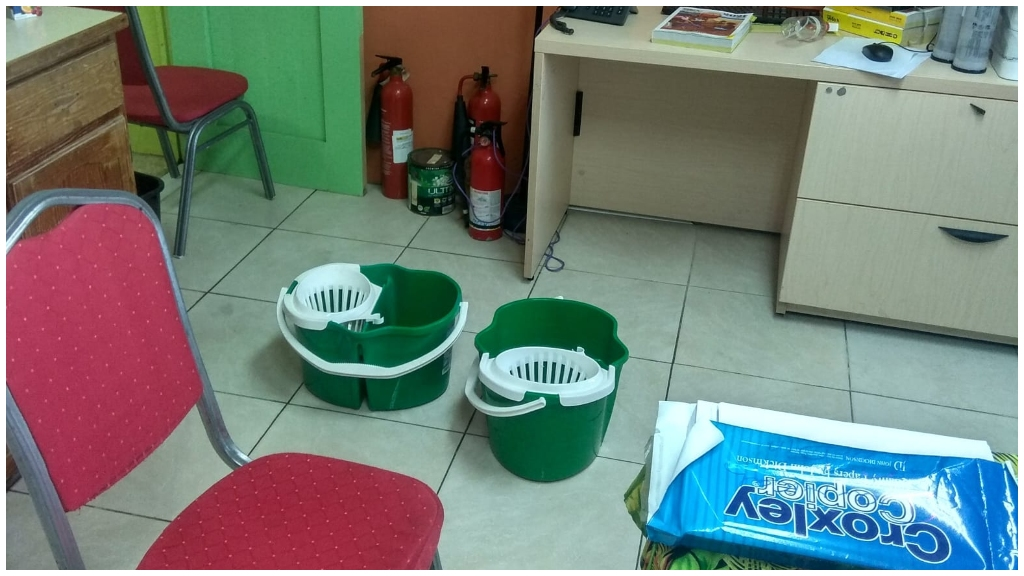 Mop buckets collecting water in one school's staff room.