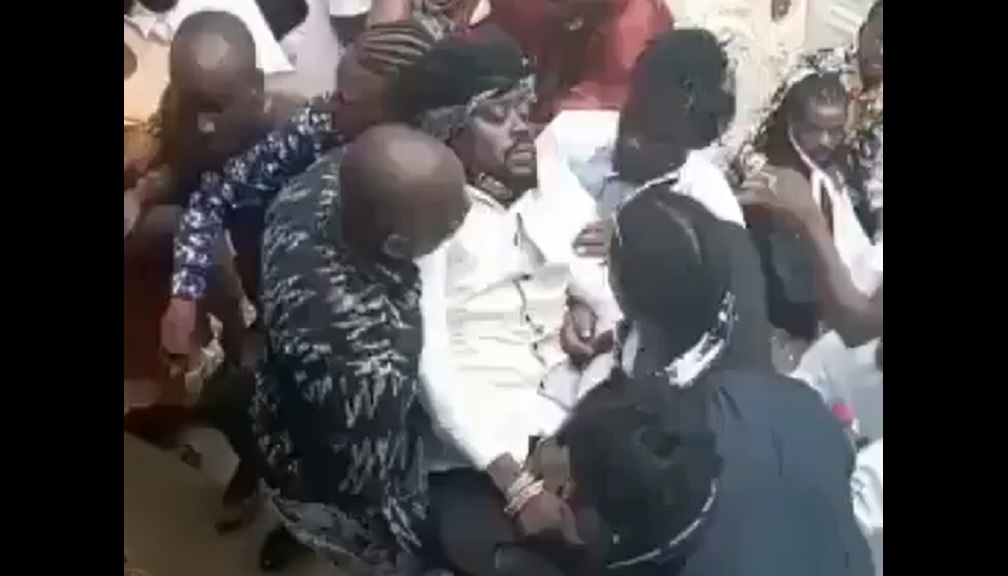 Screengrab of a video showing entertainer Beenie Man being ferried away be men after he fainted at his mother's funeral on Sunday.