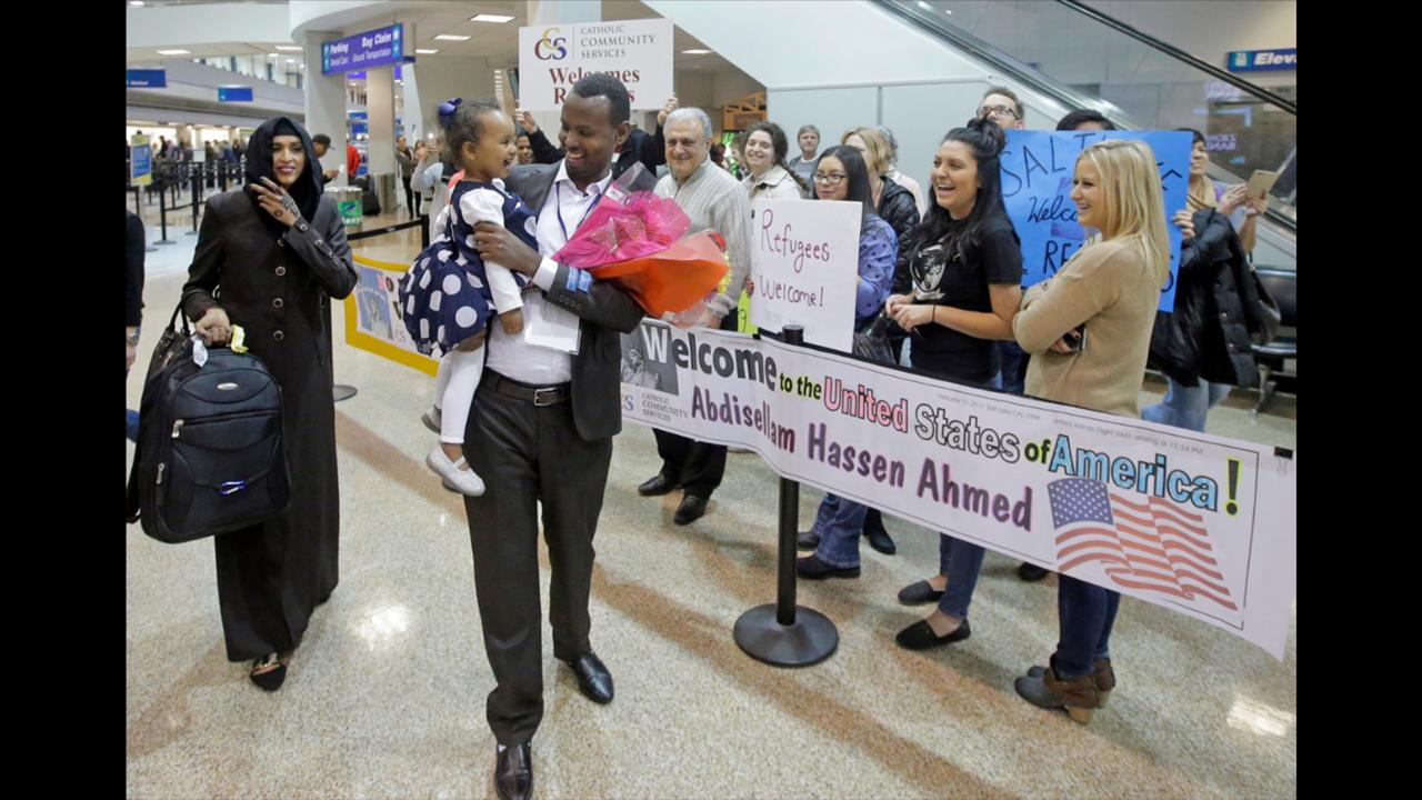 This February 10, 2017, file photo, Abdisellam Hassen Ahmed, a Somali refugee who had been stuck in limbo after President Donald Trump temporarily banned refugee entries, walks with his wife Nimo Hashi, and his 2-year-old daughter, Taslim, who he met for the first time after arriving at Salt Lake City International Airport. (AP Photo/Rick Bowmer, File)