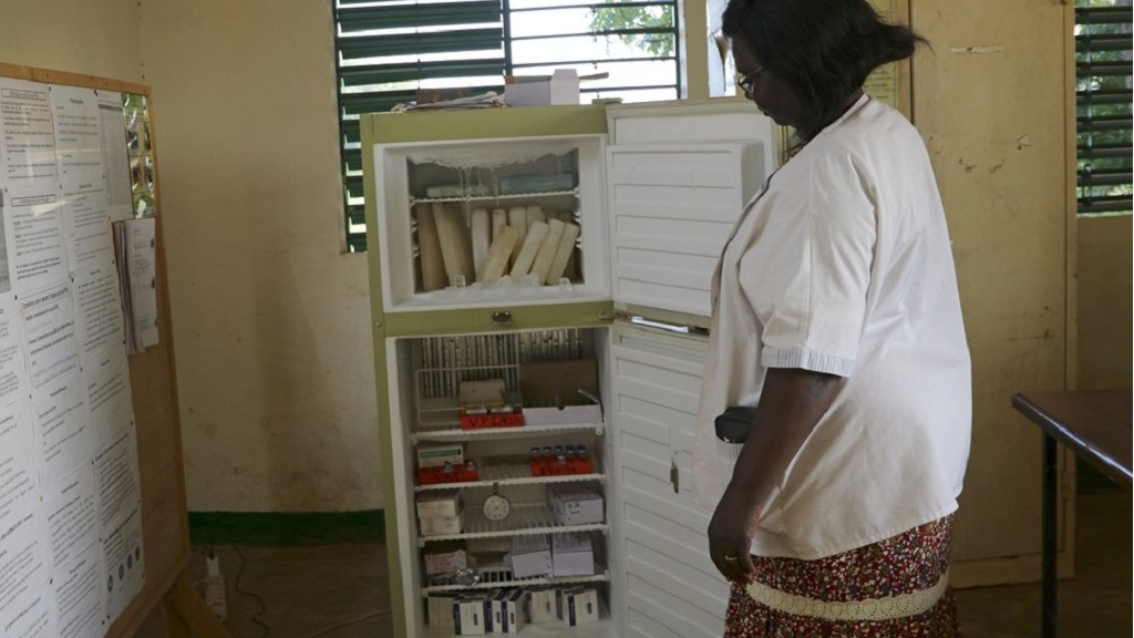 Marguerite Ouangraoua, a nurse at the health clinic in Zeguedessin village on the outskirts of Burkina Faso's capital, Ouagadougou, opens the fridge where the clinic keeps the vaccines, Thursday Oct. 8, 2020. (AP Photo/Sam Mednick)
