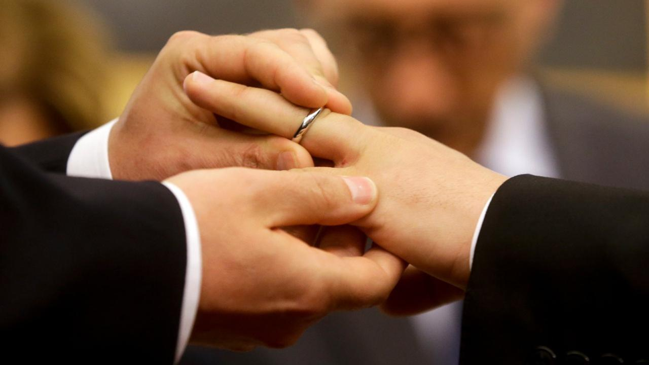 In this May 21, 2015 file photo, Mauro Cioffari, left, puts a wedding ring on his partner Davide Conti's finger as their civil union is being registered by a municipality officer during a ceremony in Rome's Campidoglio Capitol Hill. (AP Photo/Gregorio Borgia, file)