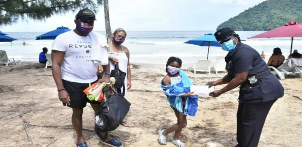 The ISOS officers rewarded beachgoers who were 'Caught in the Act' wearing their masks and observing social distancing practices while enjoying their day out. (Photo: Trinidad and Tobago Police Service)