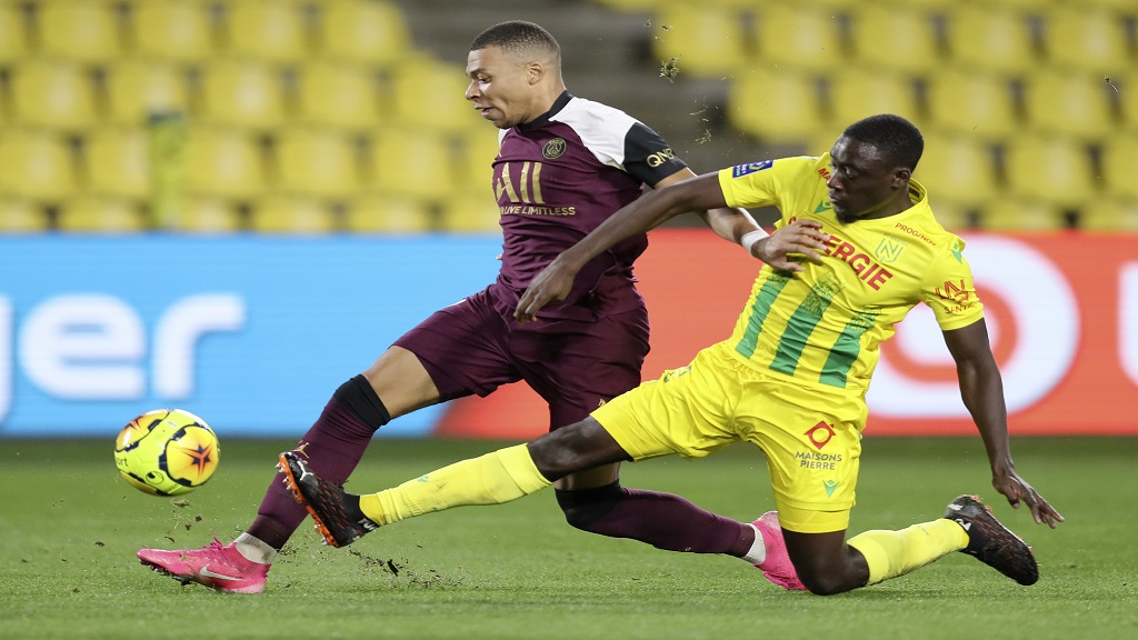 PSG's Kylian Mbappe, left, is tackled by Nantes' Dennis Appiah during a French League One football match at the Stade de la Beaujoire in Nantes, France, Saturday, Oct. 31, 2020. (AP Photo/David Vincent).