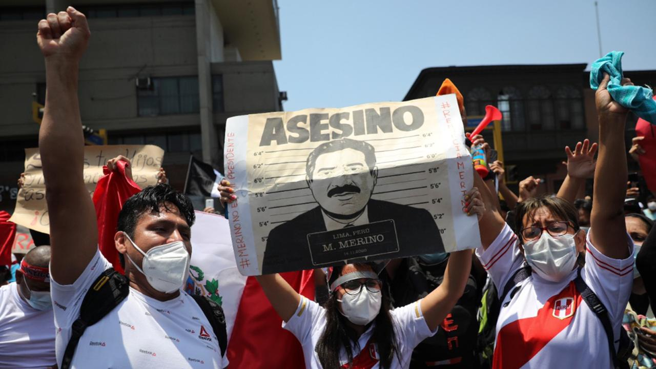 """Protesters asking that interim President Manuel Merino step down, hold a sign reading in Spanish """"Murderer"""" shortly before Merino announced his resignation in Lima, Peru, Sunday, November 15, 2020. Merino stepped down following massive protests unleashed when Congress ousted President Martin Vizcarra. (AP Photo/Rodrigo Abd)"""