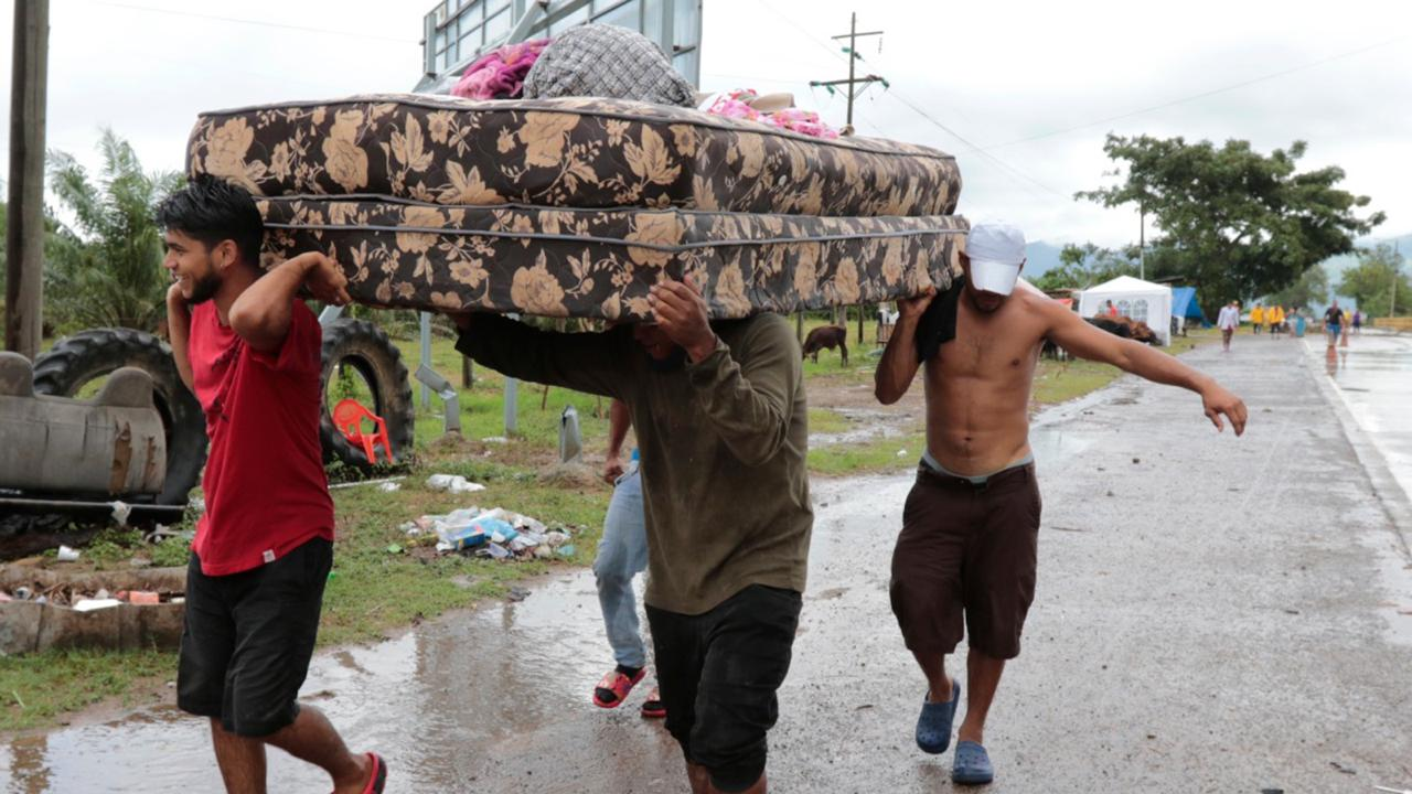 Neighbours help each other as they evacuate the area before Hurricane Iota makes landfall in San Manuel Cortes, Honduras, Monday, November 16, 2020.  (AP Photo/Delmer Martinez)