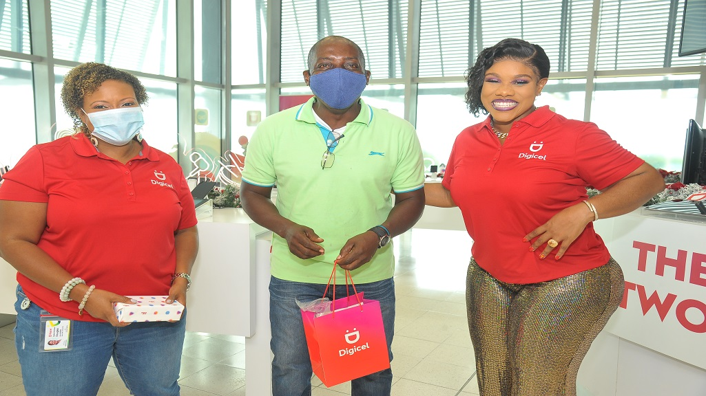 Longtime Digicel customer, Glenroy Nicholson, is all smiles after being among the first to win a prize at the launch of the Digicel Shake n Share promotion held on Thursday at the company's Iconic Store located on the Kingston Waterfront. Nicholson accepted his prize from Chief Marketing Officer for Digicel Nasha-Monique Douglas (left)  and Digicel Brand Ambassador Miss Kitty (right).