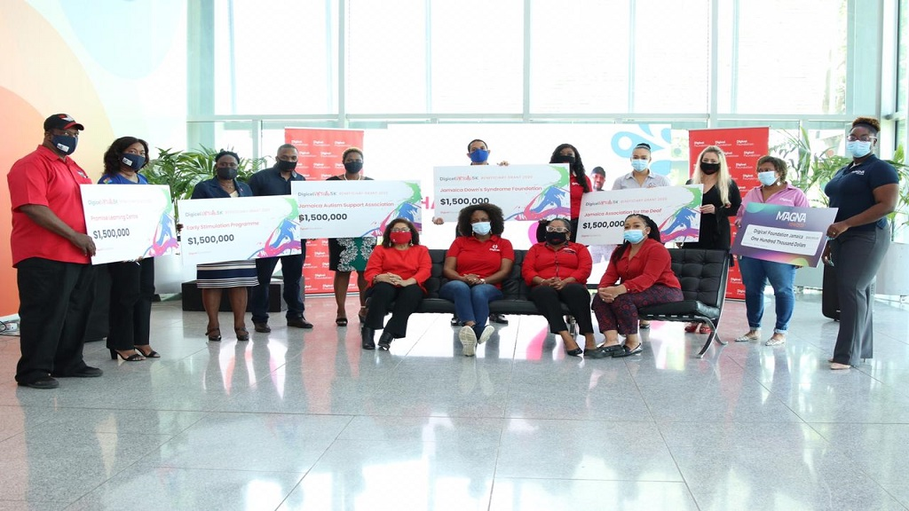 Representatives of the beneficiaries along with Digicel Foundation executives pose with the symbolic cheques at the handover ceremony on Thursday. (Photos: Marlon Reid)