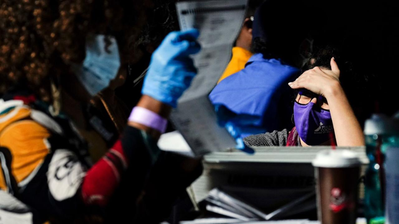 An election supervisor answer questions from an election worker as vote counting in the general election continues at State Farm Arena on Thursday, November 5, 2020, in Atlanta. (AP Photo/Brynn Anderson)