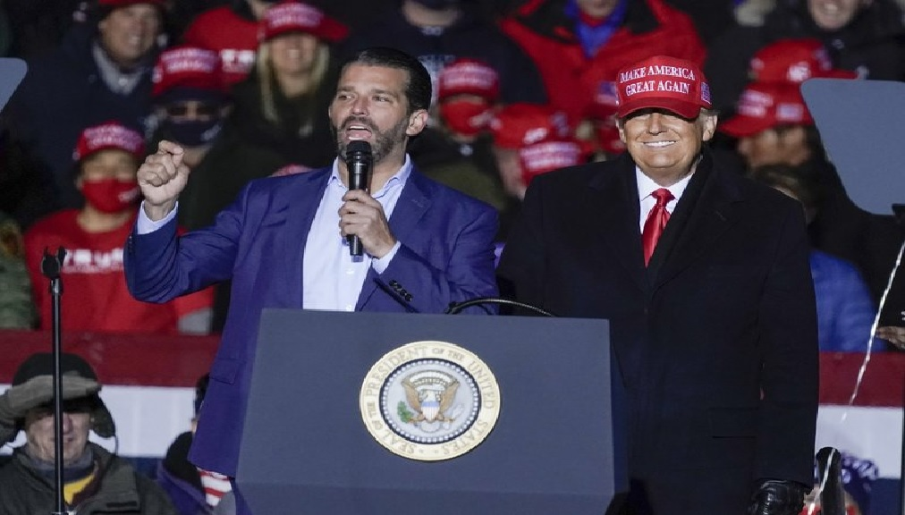 FILE - In this Nov. 2, 2020, file photo President Donald Trump watches as Donald Trump Jr. speaks at a campaign event at the Kenosha Regional Airport in Kenosha, Wis. A spokesman says President Donald Trump's eldest son, Donald Trump Jr., has been infected with the coronavirus.