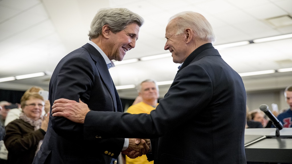 In this February 1, 2020, file photo Democratic presidential candidate former Vice President Joe Biden smiles as former Secretary of State John Kerry, left, takes the podium to speak at a campaign stop at the South Slope Community Center in North Liberty, Iowa. (AP Photo/Andrew Harnik)