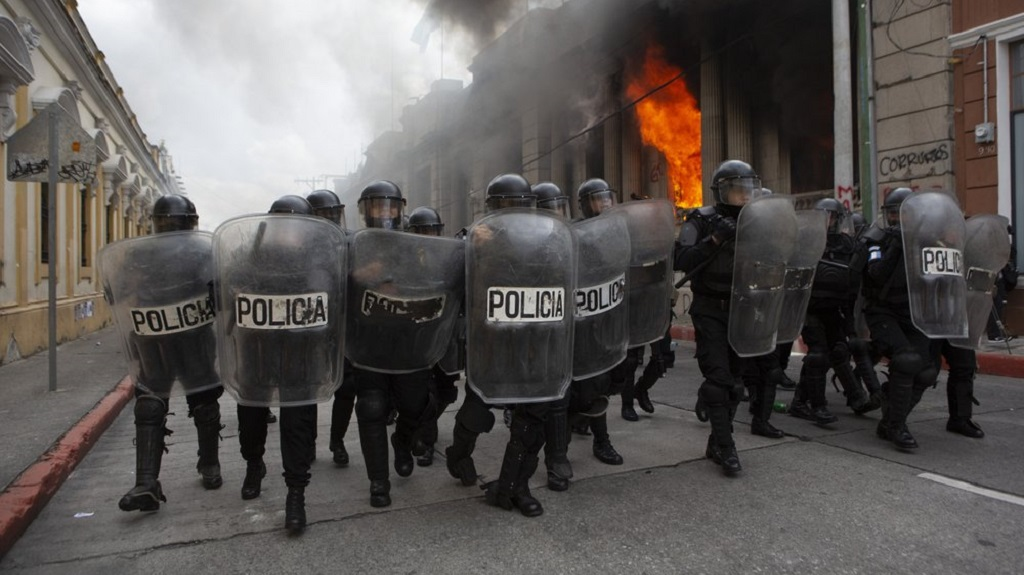 Riot police form a cordon as flames shoot out from the Congress building after protesters set a part of the building on fire in Guatemala City, Saturday, Nov. 21, 2020. Hundreds of protesters were protesting in various parts of the country Saturday against Guatemalan President Alejandro Giammattei and members of Congress for the approval of the 2021 budget that reduced funds for education, health and the fight for human rights. (AP Photo/Oliver De Ros)