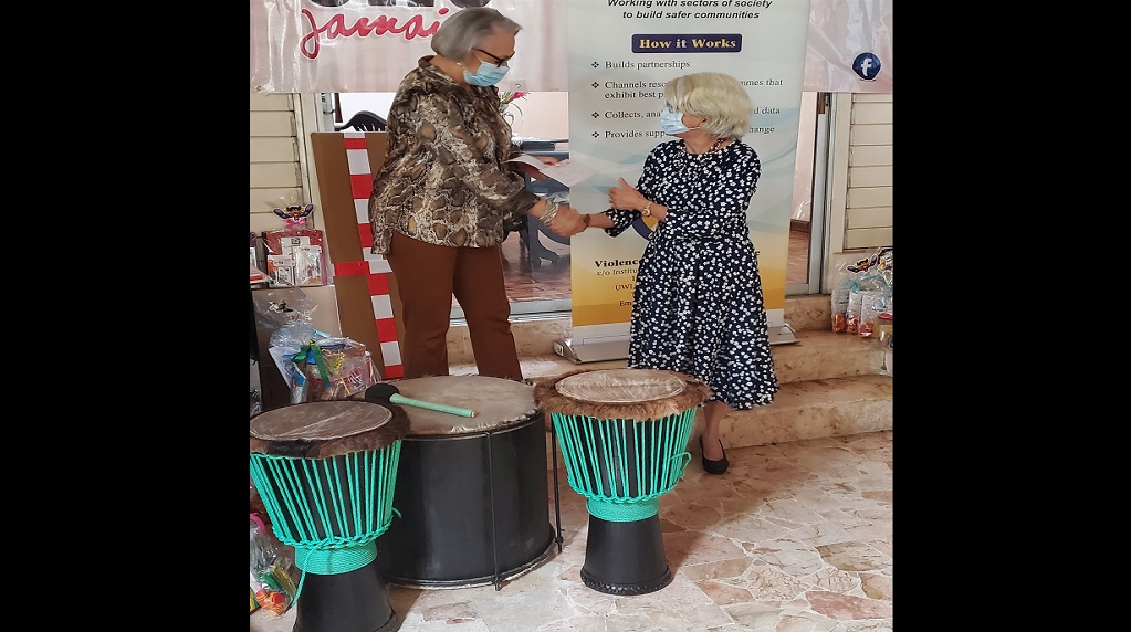 Kathryn Villeneuve (left), president of the Canadian Women's Club and friends of Jamaica presents drums to Professor Elizabeth Ward, chair of the Violence Prevention Alliance. The drums will be presented to children's homes participating in the Drum Therapy Project.