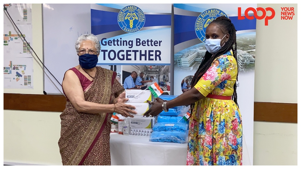 Honourary Consul to India, Dr Mohini Harris presents Louise Bobb, QEH Director of Support Services with medical supplies