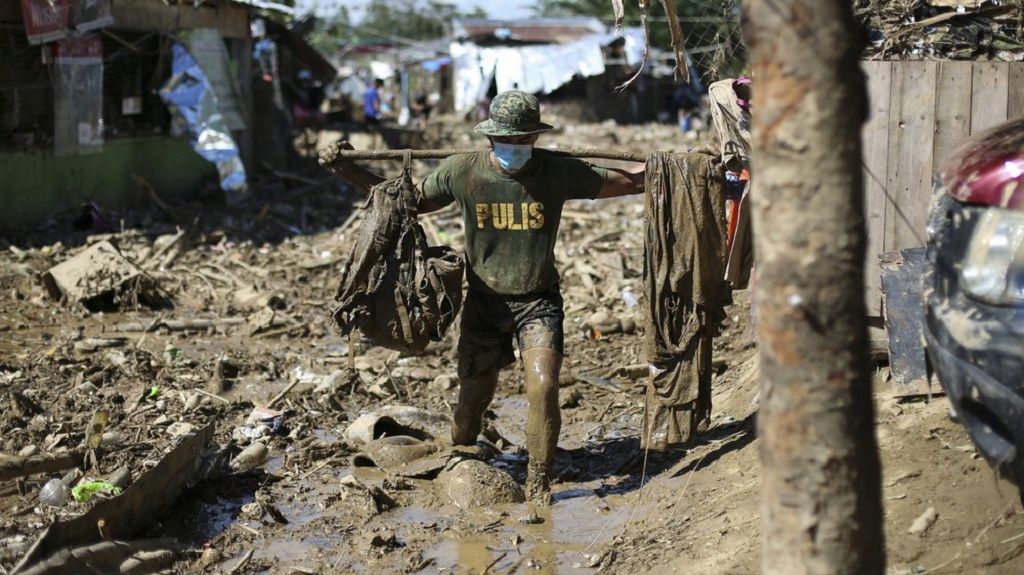 A policeman carries his belongings across debris and muds at the typhoon-damaged Kasiglahan village in Rodriguez, Rizal province, Philippines on Friday, Nov. 13, 2020. Thick mud and debris coated many villages around the Philippine capital Friday after Typhoon Vamco caused extensive flooding that sent residents fleeing to their roofs and killing dozens of people. (AP Photo/Aaron Favila)